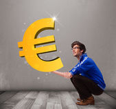 Good-looking boy holding a big 3d gold euro sign — Stock Photo