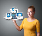 Young woman holding tablet with modern devices in clouds — Foto Stock