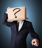 Businessman gesturing with a cardboard box on his head with ques — Stock Photo