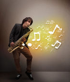 Handsome musician playing on saxophone with musical notes — Stock Photo