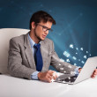 Stock Photo: Young man sitting at dest and typing on laptop with message icon