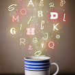 Coffee cup with colorful letters - Stock Photo