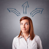 Pretty lady thinking with arrows overhead — Stock Photo