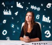 Jonge zakenvrouw zit aan bureau met diagrammen en statistieken — Stockfoto