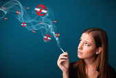 Young woman smoking dangerous cigarette with no smoking signs — Stock Photo