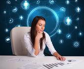Empresária sentado na mesa com ícones de redes sociais — Fotografia Stock