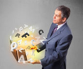 Middle aged businessman holding laptop with colorful letters — Stockfoto