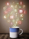 Coffee cup with colorful letters — Stock Photo