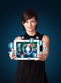 Young woman holding tablet with social network icons — Stok fotoğraf