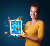 Woman holding modern tablet with colorful diagrams and graphs — Stok fotoğraf