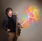 Attractive musician playing on saxophone with colorful abstract — Foto de Stock