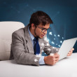 Angry man sitting at dest and typing on laptop with message icon — Stock Photo