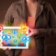 Girl presenting a tablet with colorful social icons and signs — Stockfoto