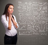 Pretty woman looking at stock market graphs and symbols — Stock Photo