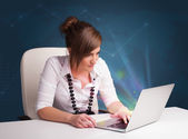 Beautiful woman sitting at desk and typing on laptop with abstra — Stock Photo