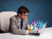 Hombre guapo sentado en el escritorio y escribiendo en el ordenador portátil con 3d número — Foto de Stock