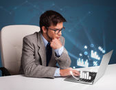 Young man sitting at desk and typing on laptop with diagrams and — Stock Photo