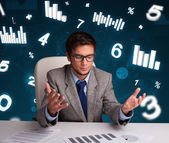 Businessman sitting at desk with diagrams and statistics — Stock Photo