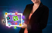Lady holding a tablet with modern colorful apps and icons — Stok fotoğraf