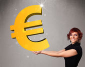Beautiful girl holding a big 3d gold euro sign — Stock Photo