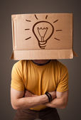 Young man gesturing with a cardboard box on his head with light — Stock Photo