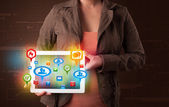 Girl presenting a tablet with colorful social icons and signs — Stock Photo