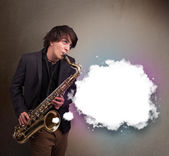 Young man playing on saxophone with copy space in white cloud — Stock Photo