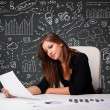 Businesswomsitting at desk with business scheme and icons — Stock Photo #27425723