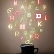 Coffee cup with colorful letters — Stock Photo #27426413