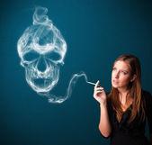 Young woman smoking dangerous cigarette with toxic skull smoke — Stock fotografie