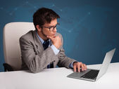 Young man sitting at desk and typing on laptop — Stock Photo