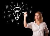 Woman drawing light bulb on whiteboard — Stock Photo