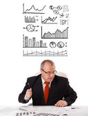 Businessman sitting at desk with statistics and graphs — Stock Photo
