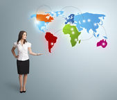 Young woman presenting colorful world map — Stock Photo