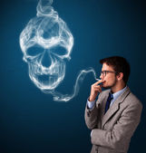 Young man smoking dangerous cigarette with toxic skull smoke — Stock Photo