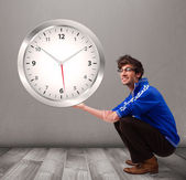 Attractive boy holding a huge clock — Stock Photo