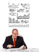 Businessman sitting at desk with statistics and graphs — Stok fotoğraf