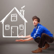 Young boy holding a huge drawn house — Stock Photo