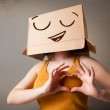 Young woman gesturing with a cardboard box on her head with smil — Stock Photo