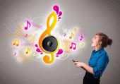 Söt flicka sjunga och lyssna på musik med musiknoter — Stockfoto