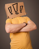 Young man gesturing with a cardboard box on his head with exclam — Stock Photo