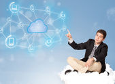 Happy businessman sitting on cloud with cloud computing — Stock Photo