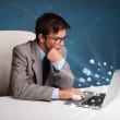 Young man sitting at dest and typing on laptop with message icon — Stock Photo