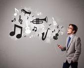 Attraktiver junger mann singen und hören von musik mit musical — Stockfoto