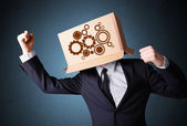 Businessman gesturing with a cardboard box on his head with spur — Stock Photo