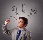 Young man thinking with question marks overhead — Stock Photo
