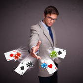 Young man playing with poker cards and chips — ストック写真
