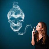Cigarro perigoso de mulher jovem fumar com fumaça tóxica de crânio — Fotografia Stock