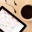 Tablet pc showing calendar on screen with a cup of coffee on a d — Stock Photo #29666735