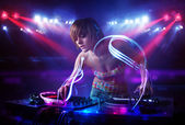 Disc jockey girl playing music with light beam effects on stage — Stock Photo